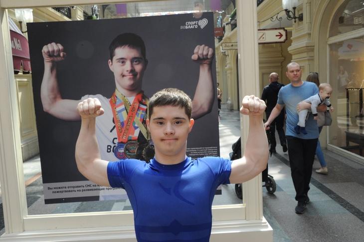 Влад Ситдиков рядом со своим фотопортретом на выставке «Спорт во благо. Дети»